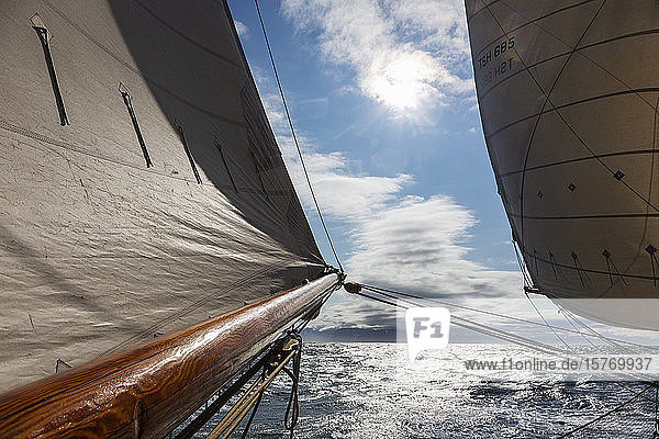 Sail and wooden sailboat mast over sunny tranquil Atlantic Ocean
