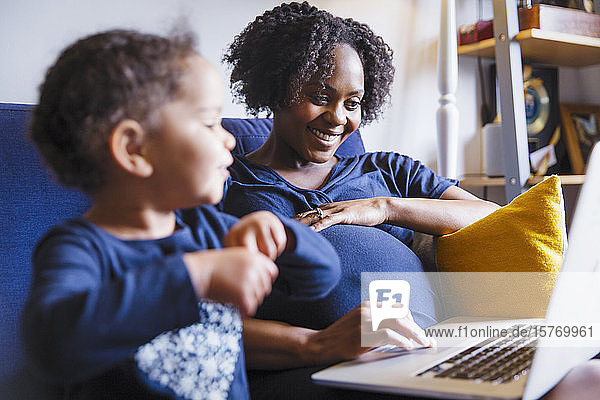 Happy pregnant woman with daughter using laptop on sofa