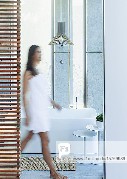 Woman wrapped in a towel walking in luxury  modern bathroom