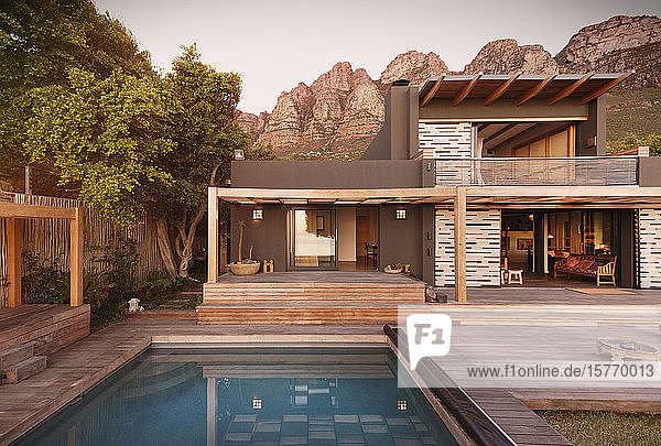 Mountains behind modern  luxury home showcase exterior house with swimming pool