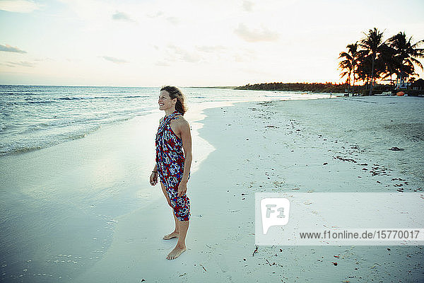 Carefree woman in sun dress on tranquil ocean beach Mexico