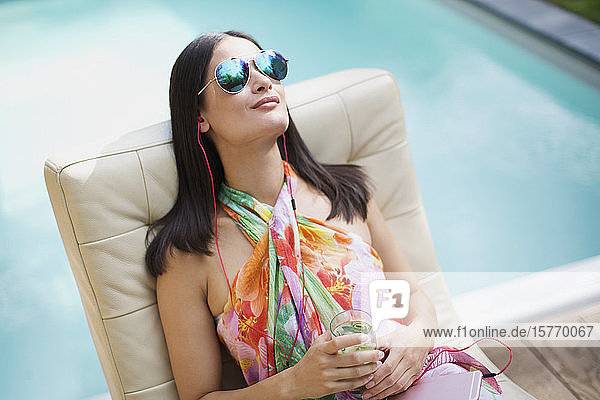 Serene woman with sunglasses and headphones relaxing  listening to music at summer poolside