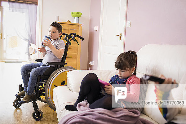 Boy with Down Syndrome in wheelchair and sister in living room