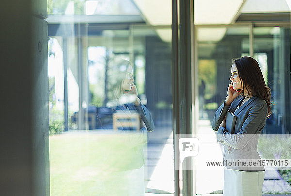 Businesswoman talking on smart phone at window
