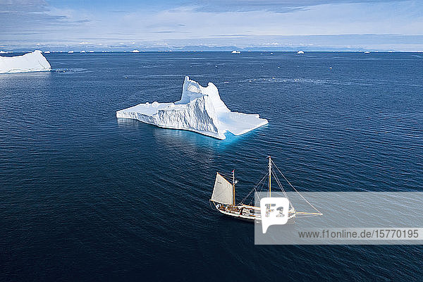Ship sailing past iceberg on sunny blue Atlantic Ocean Greenland