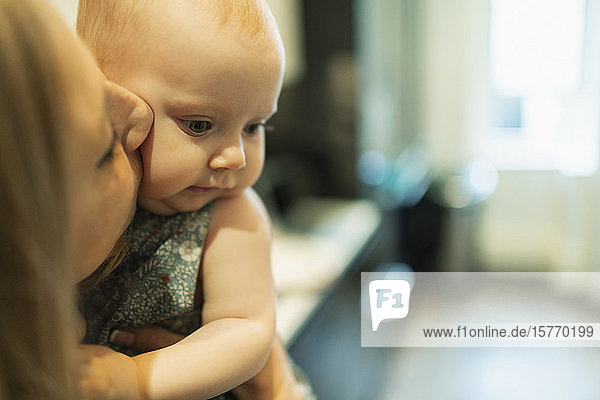 Close up mother kissing cute baby daughter