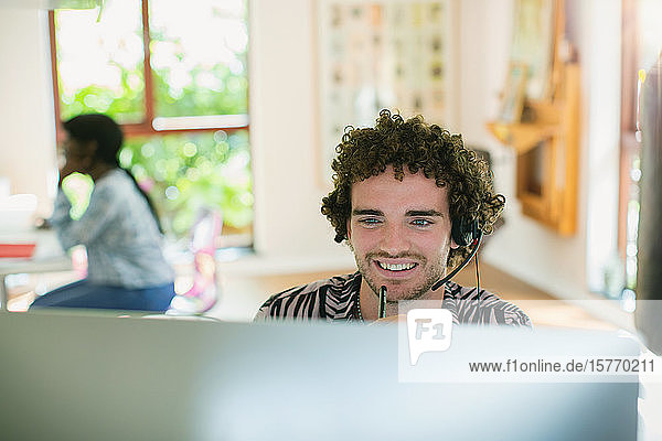 Young man with headset working at computer in home office