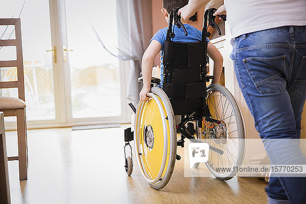 Boy pushing brother in wheelchair