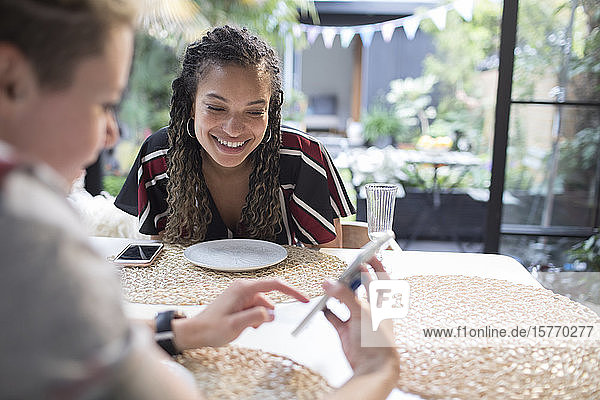 Young women friends using smart phone at dining table