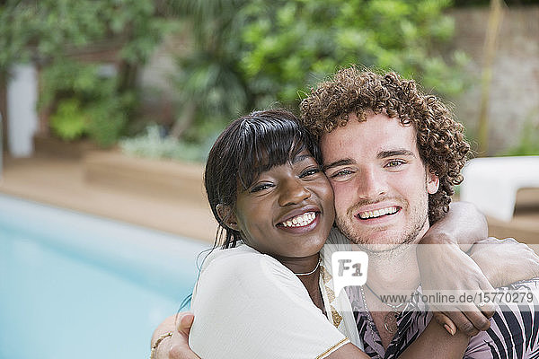 Portrait happy young multiethnic couple hugging at poolside