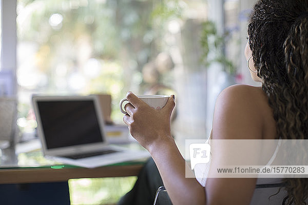 Young woman drinking tea at laptop in home office