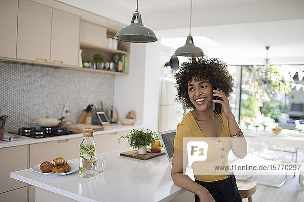 Happy young woman talking on smart phone in kitchen