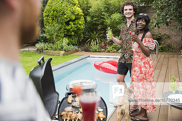 Happy young couple enjoying cocktails and barbecuing at poolside