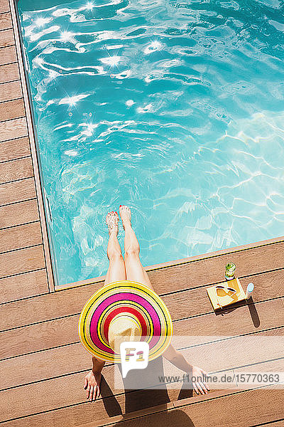 Woman in sun hat relaxing at sunny summer poolside