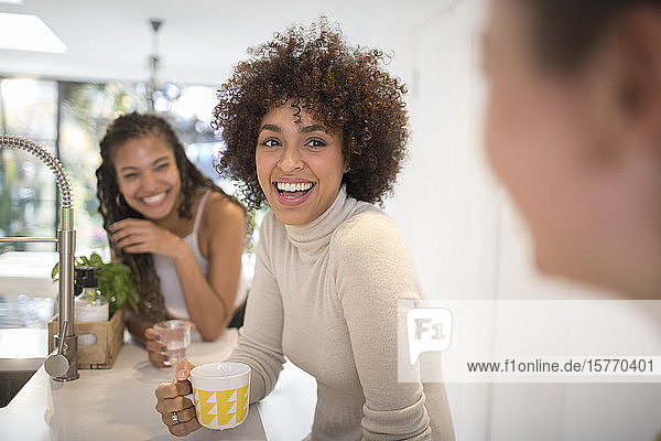 Happy young women friends laughing and drinking tea in kitchen
