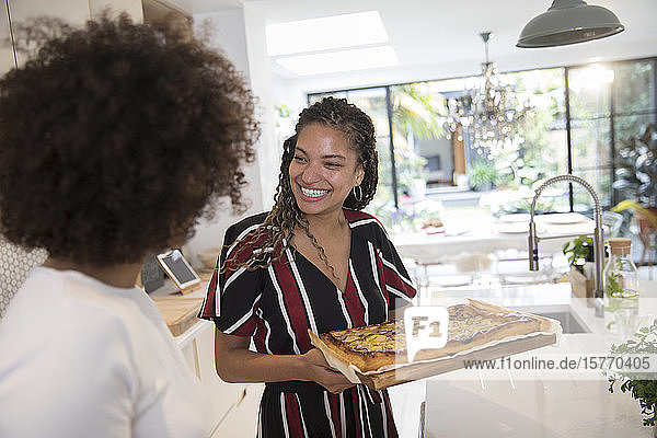 Happy young women friends with homemade pizza in kitchen