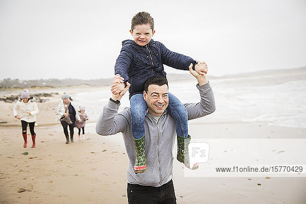 Portrait playful father carrying son on shoulders on winter beach
