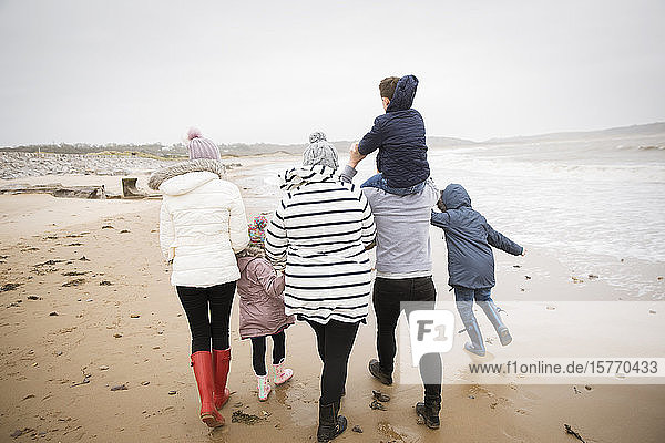 Family in warm clothing walking on winter ocean beach