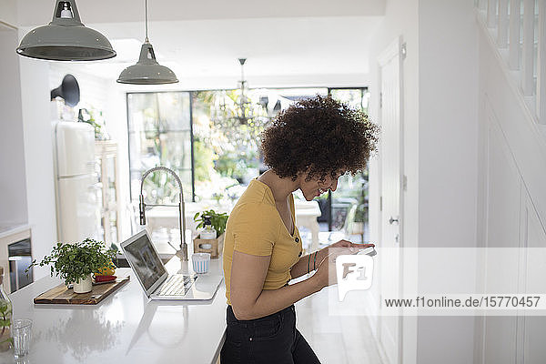 Young woman texting with smart phone in kitchen