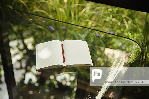 Notebook open to blank pages on glass table