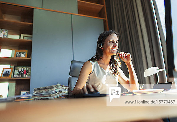 Smiling female interior designer with headset working in home office