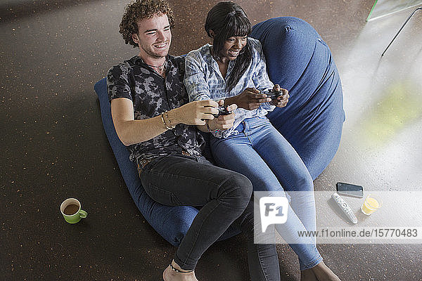 Happy young couple playing video game on beanbag chair