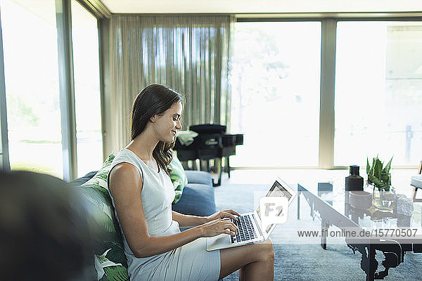 Businesswoman working from home  using laptop on sofa