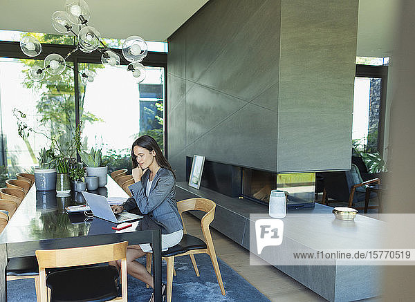 Businesswoman working from home  using laptop at dining table