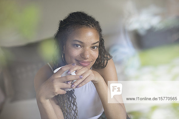 Portrait smiling confident young woman drinking coffee