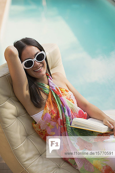 Portrait happy woman relaxing  reading book on lounge chair at summer poolside