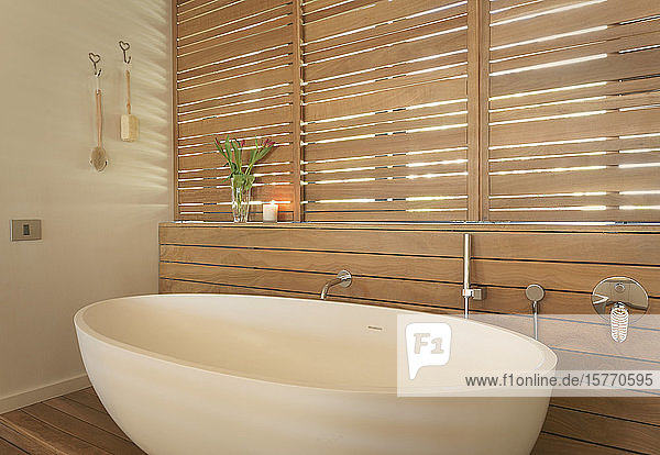 Soaking tub and wood shutters in modern  luxury home showcase interior bathroom