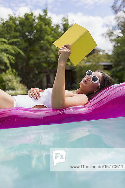 Woman relaxing  reading book on inflatable raft in summer swimming pool