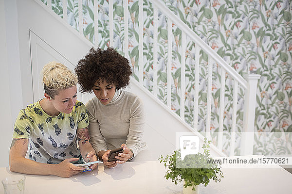 Young women friends using smart phones in kitchen