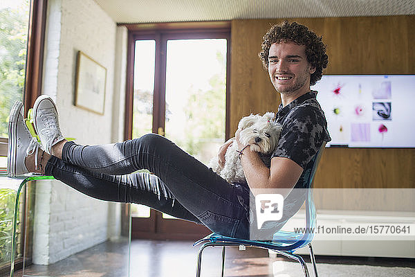 Portrait happy young man with dog in home office