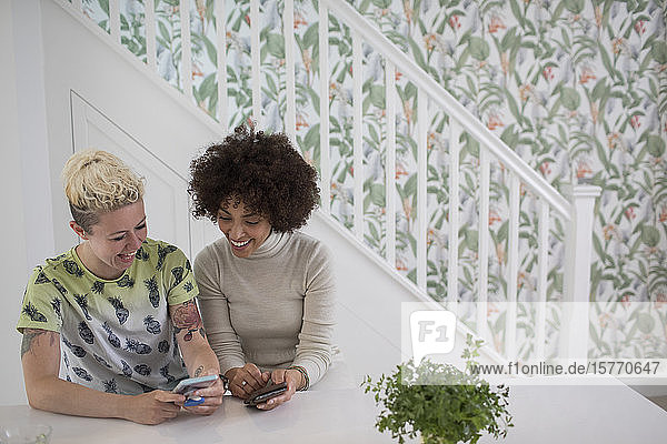 Happy young woman using smart phones in kitchen