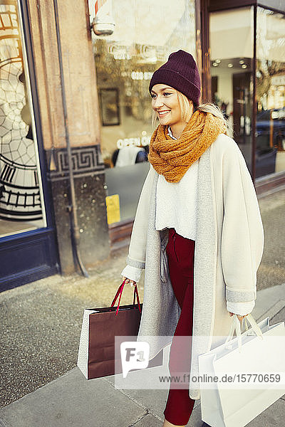 Young woman in stocking cap and scarf walking with shopping bags on sidewalk