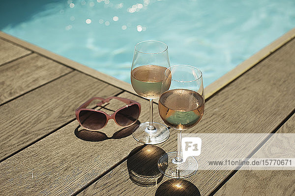 Rose wine glasses and sunglasses at sunny poolside