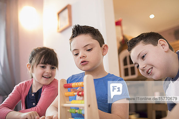 Boy with Down Syndrome and siblings playing with toy
