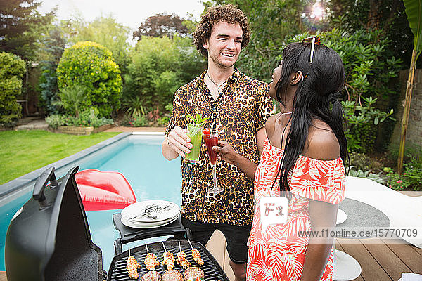 Happy young couple drinking cocktails at poolside barbecue