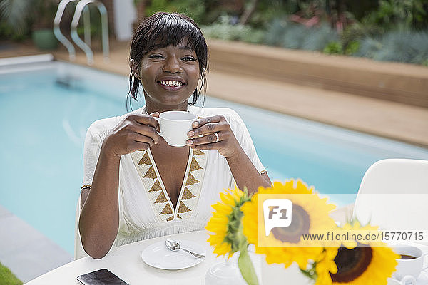 Portrait happy young woman drinking coffee at poolside