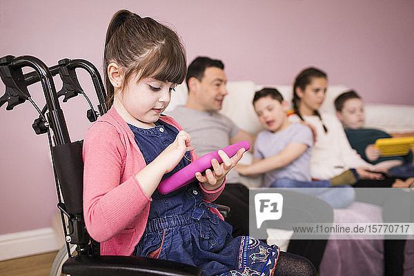 Girl with Down Syndrome in wheelchair using digital tablet