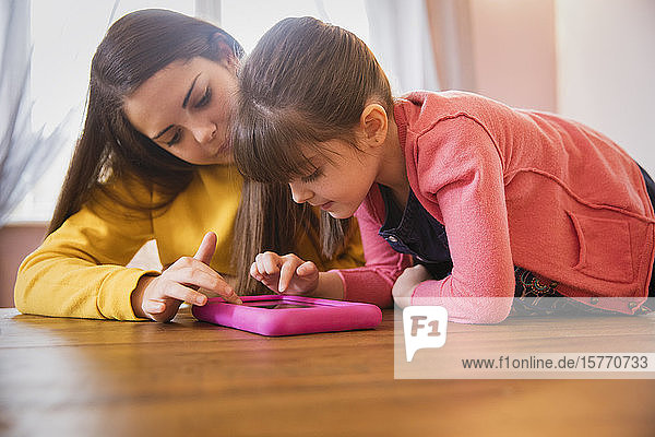 Teenage girl and sister with Down Syndrome using digital tablet