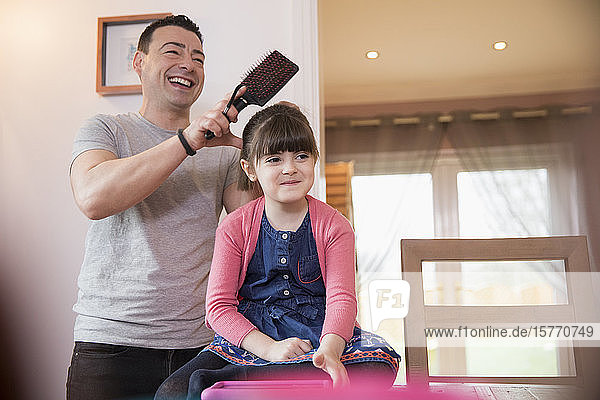Father brushing hair of daughter with Down Syndrome