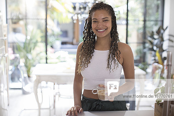 Portrait happy young woman drinking coffee in kitchen