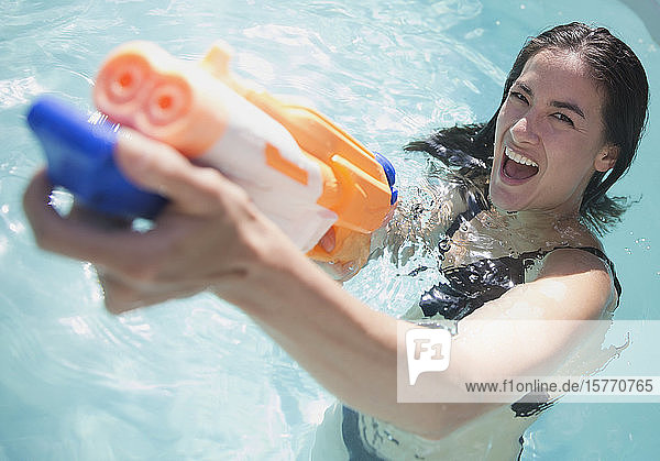 Portrait playful woman with squirt gun in sunny swimming pool