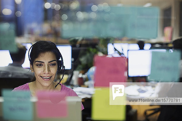 Businesswoman with headset working at computer in office behind adhesive notes