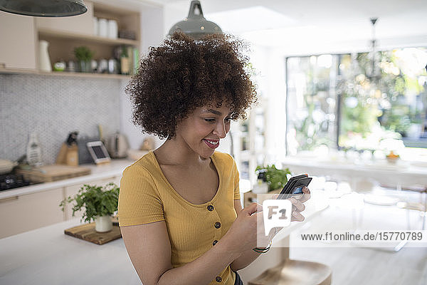 Smiling young woman using smart phone in kitchen