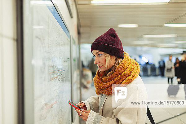 Young woman with smart phone checking subway map