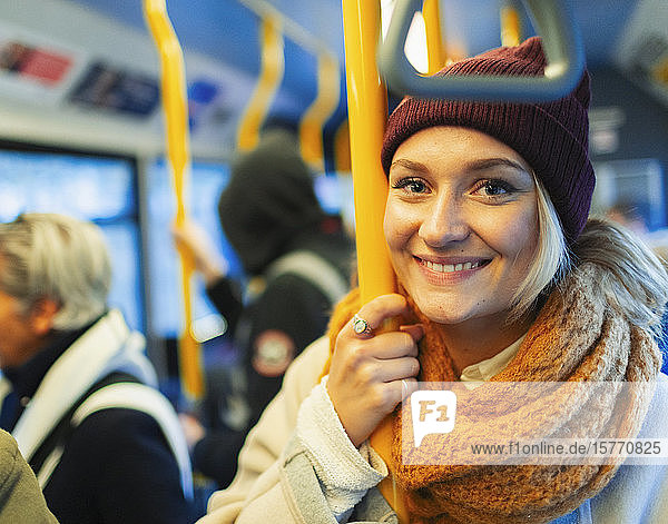 Portrait confident young woman wearing stocking cap and scarf riding bus
