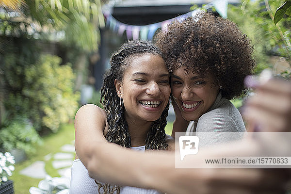 Happy young women friends taking selfie with camera phone
